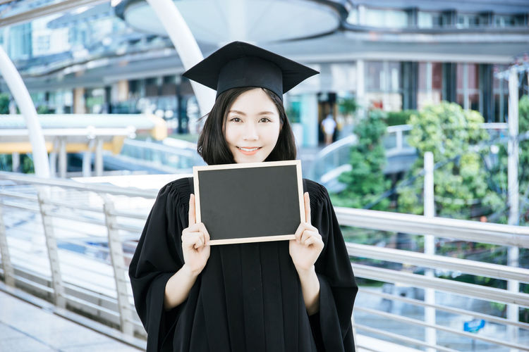 Portrait Of Woman Wearing Graduation Gown While Standing On Bridge