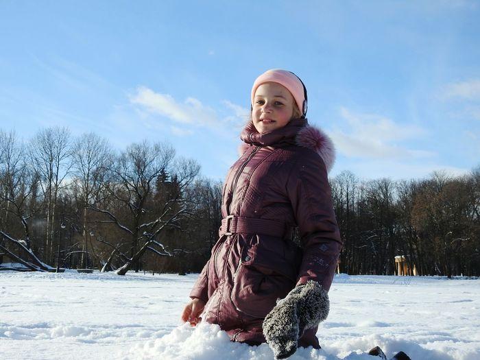 Portrait of smiling girl kneeling on snow covered field against blue sky