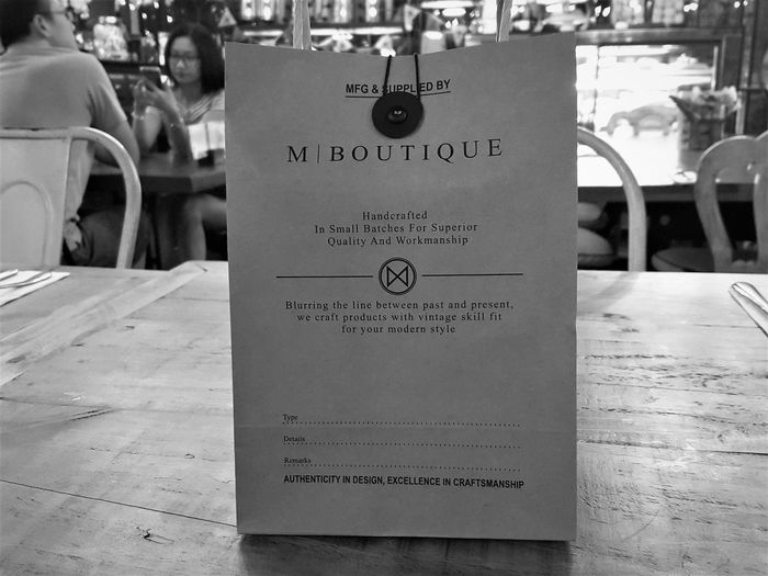 M Boutique paper bag M Boutique Hotel Paper Bag Chair Information Information Sign Message Paper Restaurant Seat Table Text
