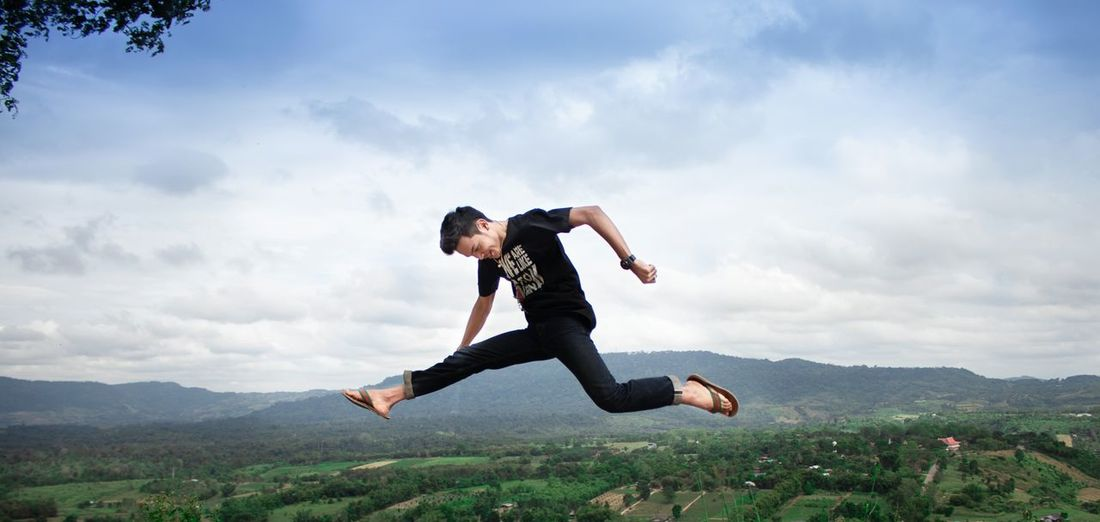 Side view of young man jumping against mountain