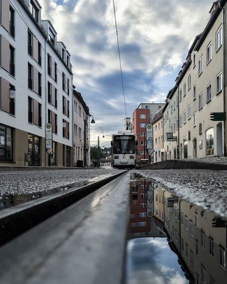 Reflection of buildings on puddle against cable car on street