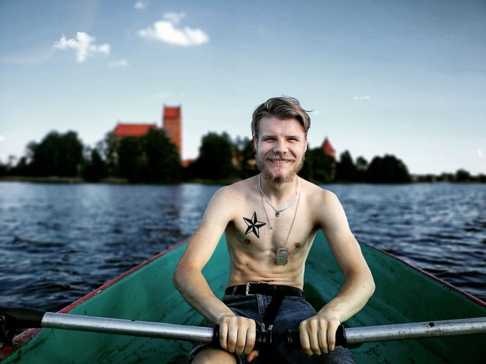 Portrait of smiling shirtless young man rowing boat in river