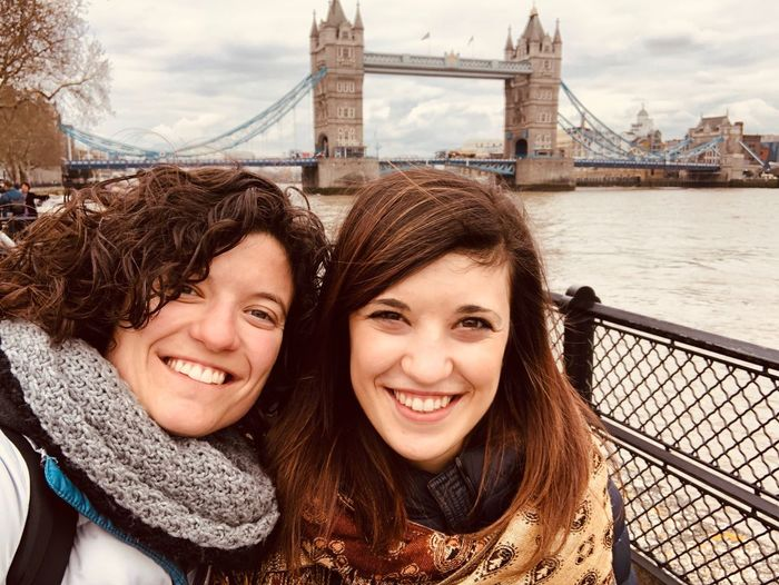 Portrait of smiling friends in city with bridge in background