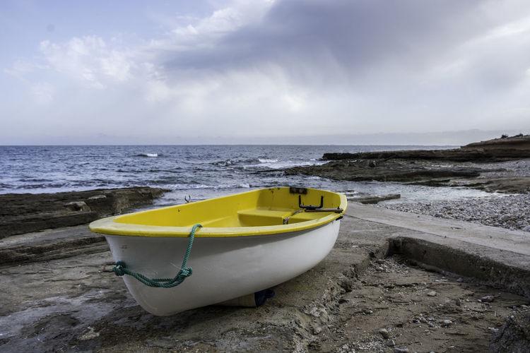 Boat moored on beach against sky