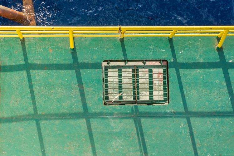 The Color Of Business Yellow Blue Green Color No People Dramatic Angles Handrail  Sea Ocean Side Offshore Offshore Life Offshore Work Workplace Shadow Oil And Gas Oil And Gas Industry Installation Barge Deck Work Manhole  Grating