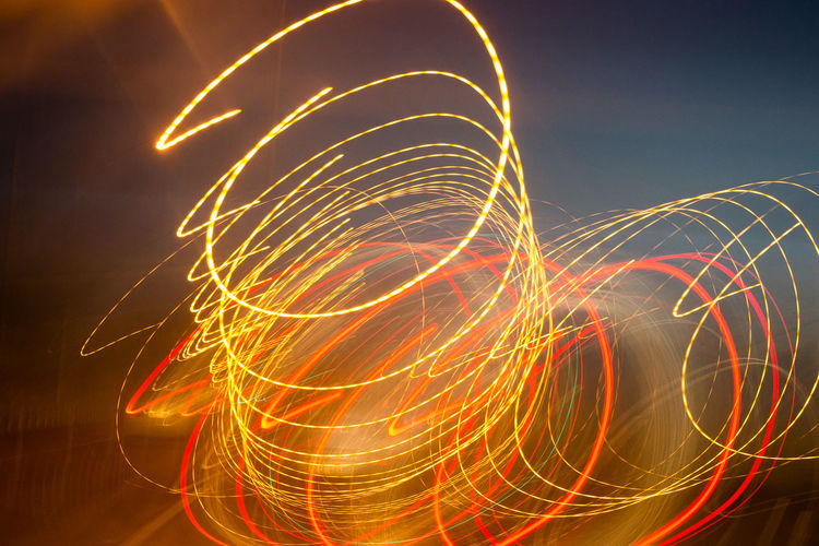 Long Exposure Motion Illuminated Blurred Motion Glowing Night Light Trail Light Painting Pattern Sky Abstract Speed Creativity No People Orange Color Nature Light - Natural Phenomenon Multi Colored Wire Wool Red Light Sparks