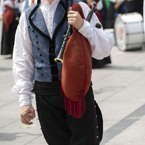 Man is holding a bagpipe, spanish traditional dance group Asturias Holiday Man Music SPAIN Sunny Traditional Clothing Bagpipe City Day Hand Holding Lifestyles Musical Instrument Outdoors Performance Pipe Band Real People Square Format Standing Street Summer Traditional