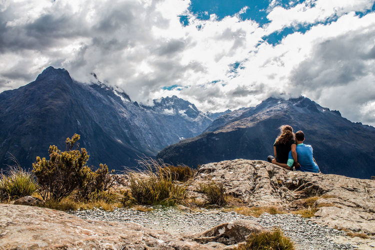 Rear view of couple sitting on mountain against cloudy sky