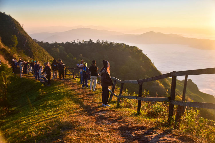 People walking on ridge against sky during sunset