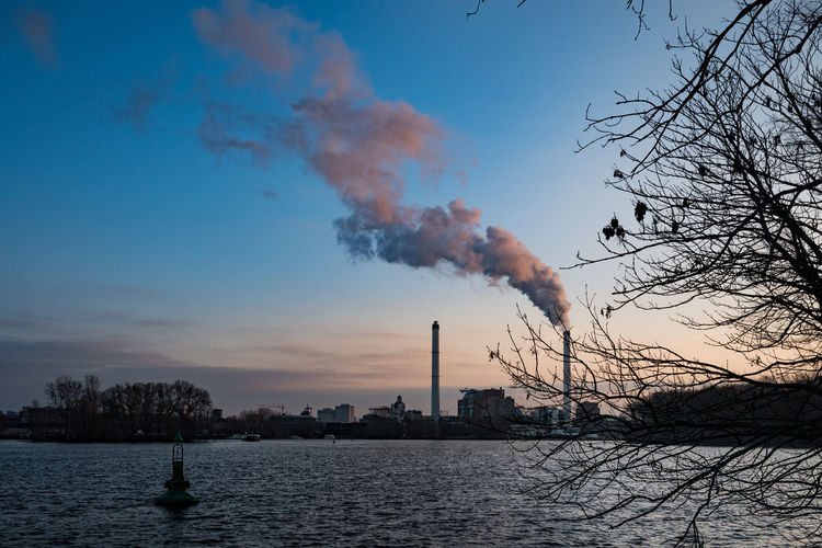 Smoke emitting from chimney by river against sky