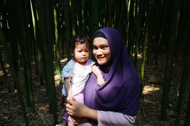 Woman carrying daughter while standing at bamboo grove
