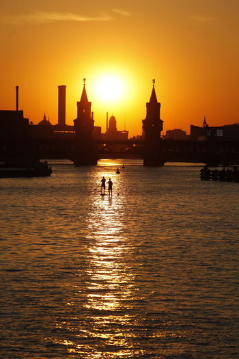 Architecture Beauty In Nature Building Exterior Built Structure City Dome Nature Oberbaumbrücke Orange Color Outdoors Place Of Worship Real People Reflection River Silhouette Sky Spirituality Spree River Sun Sunset Tourism Transportation Travel Destinations Water Waterfront