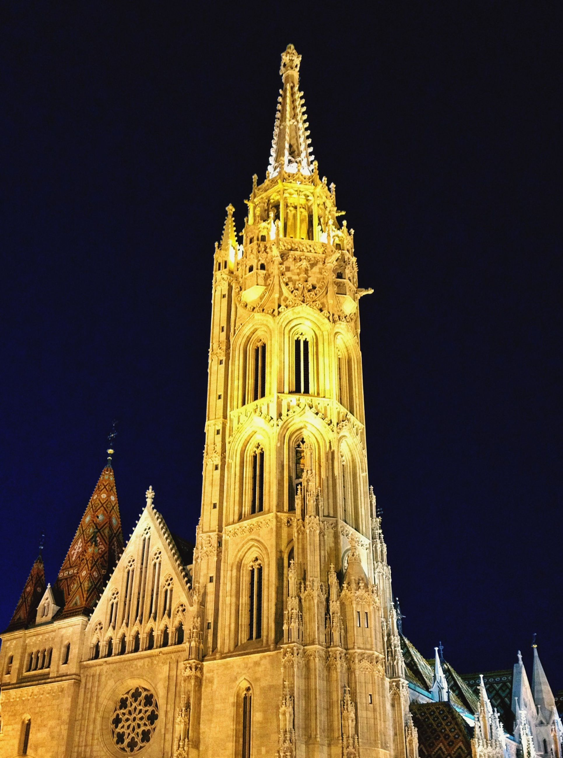 low angle view, architecture, religion, place of worship, building exterior, built structure, spirituality, famous place, travel destinations, clear sky, international landmark, travel, night, tourism, cathedral, church, capital cities, blue, illuminated