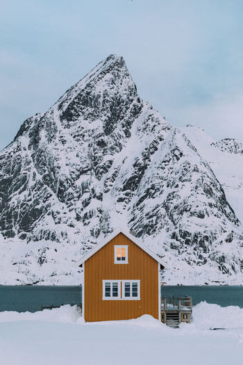 House on snow covered mountain against sky