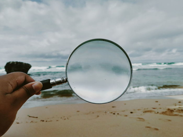 Beach Cloud - Sky Day Finger Focus On Foreground Hand Holding Human Body Part Human Hand Land Magnifying Glass Nature One Person Outdoors Real People Sea Sky Transparent Unrecognizable Person Water