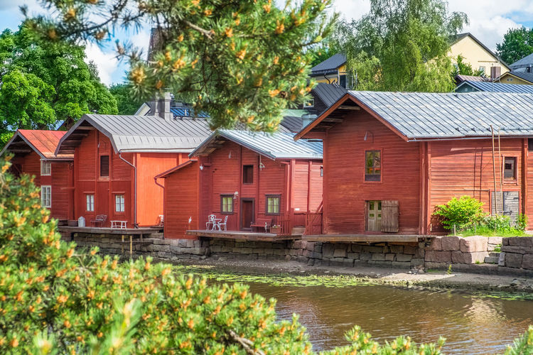Beautiful city landscape with idyllic river and old buildings at summer day in Porvoo, Finland Architecture Built Structure Building Building Exterior House Tree Plant Water Nature River Day Residential District No People Growth Outdoors Green Color Waterfront Old Vintage Wood - Material Finland Summer Bright Pine Tree Land Landscape City Village Town Travel Destinations Tourism Landmark Famous Place History Traditional Idyllic Porvoo