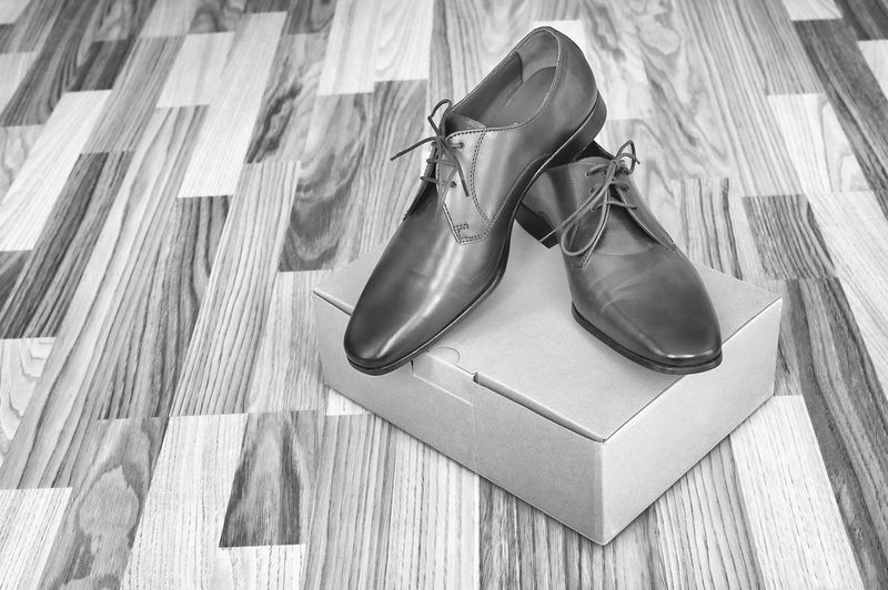 High angle view of formal shoes over box on hardwood floor