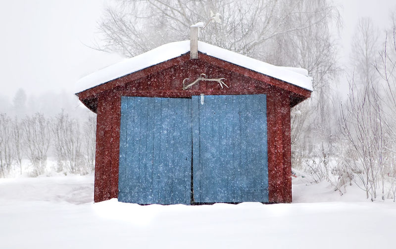 Snow covered house against bare trees during winter