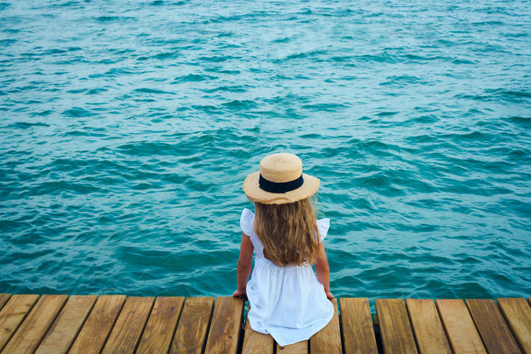 Child in straw hat on sea shore, look from behind