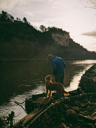 Man with dog on lake against sky
