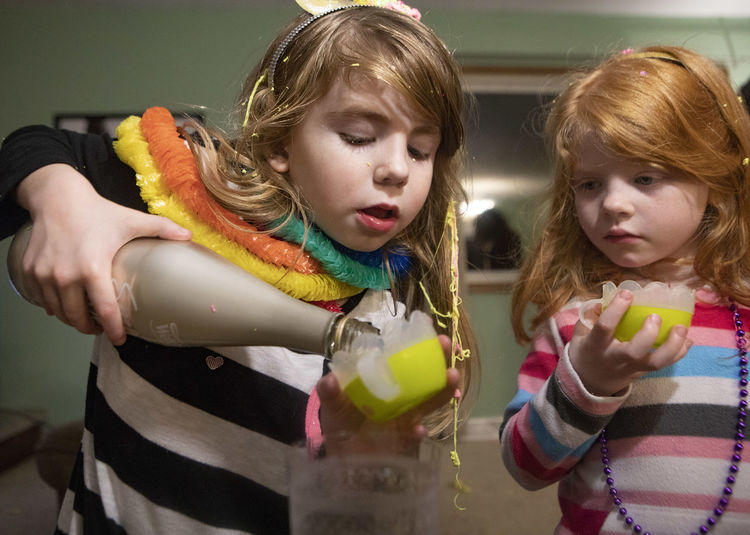 A seven-year-old girl pours grape juice on New Year's Even while her sister looks on. Childhood Child Girls Women Casual Clothing Indoors  Innocence Females Togetherness Food And Drink Friendship Looking Two People Real People Lifestyles Hairstyle Drinking Sister Family New Year's Eve New Year's Eve 2019 Sparkling Grape Juice Beverage Celebration