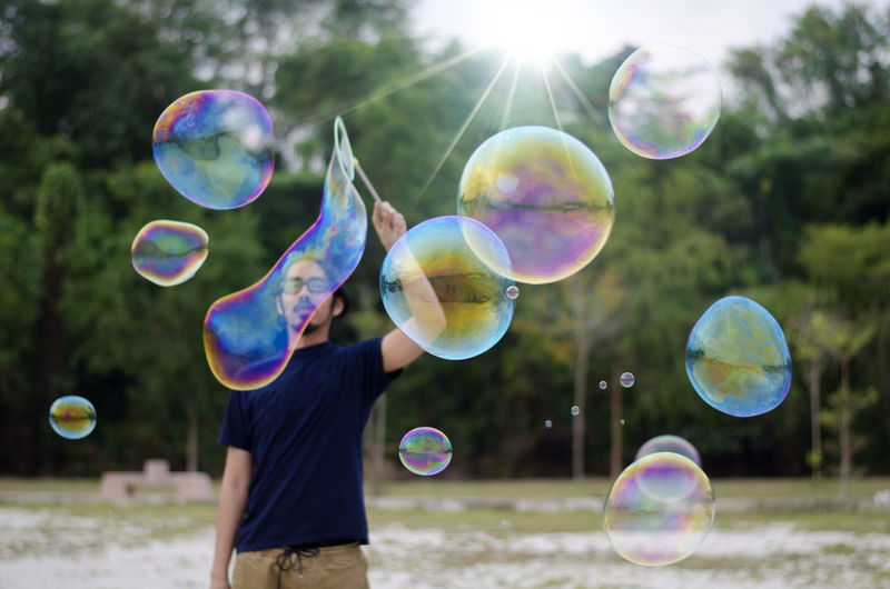 Mature man making bubbles while standing against trees