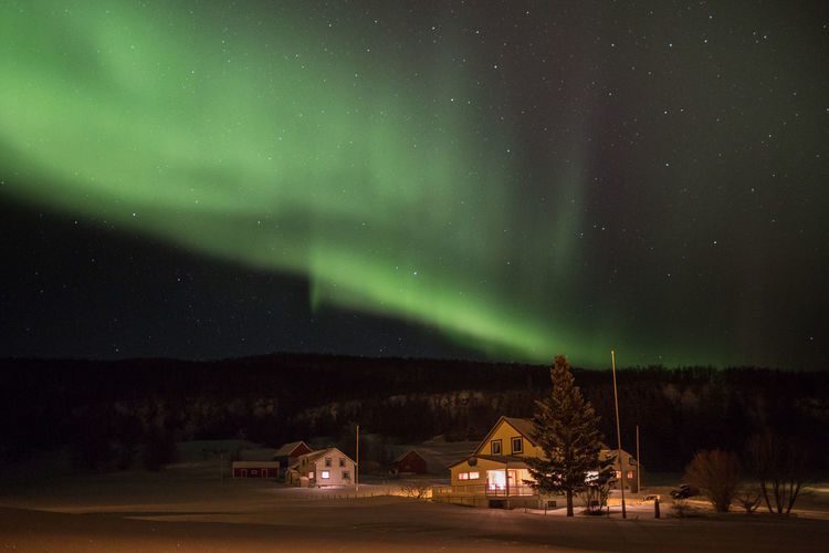 Houses Against Aurora Borealis At Night During Winter