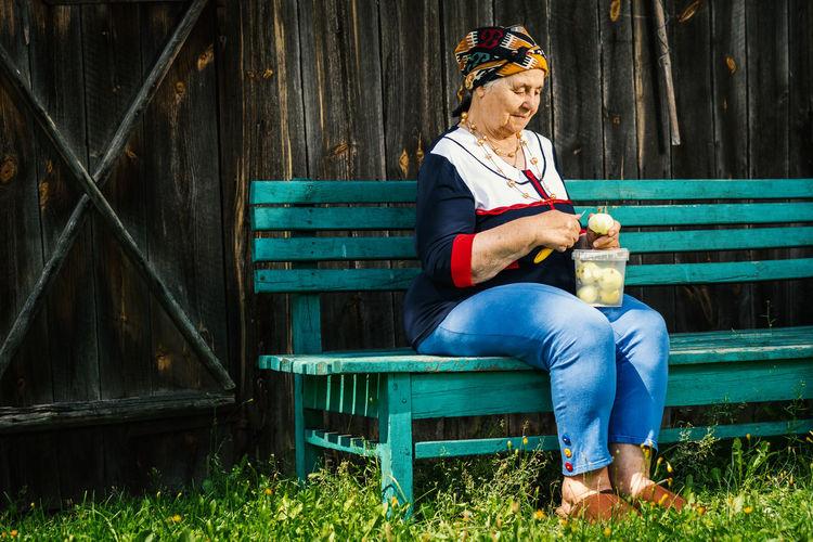 Senior woman peeling apple while sitting on bench at park