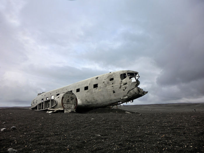 Abandoned Airplane On Field Against Cloudy Sky