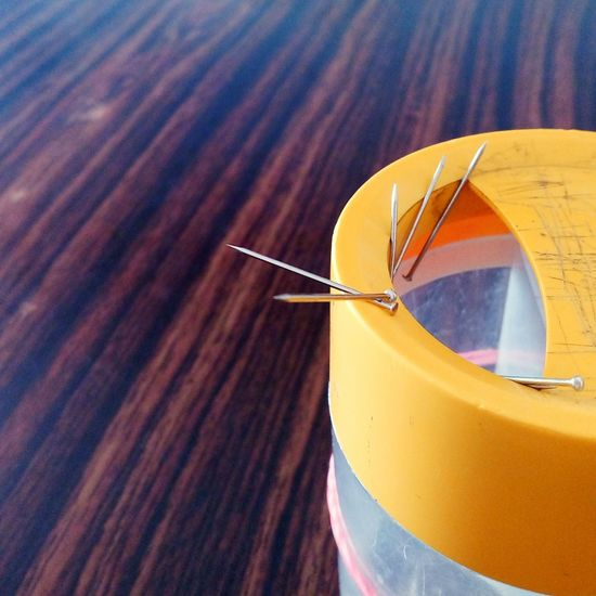 Close-Up Of Straight Pins In Container On Table