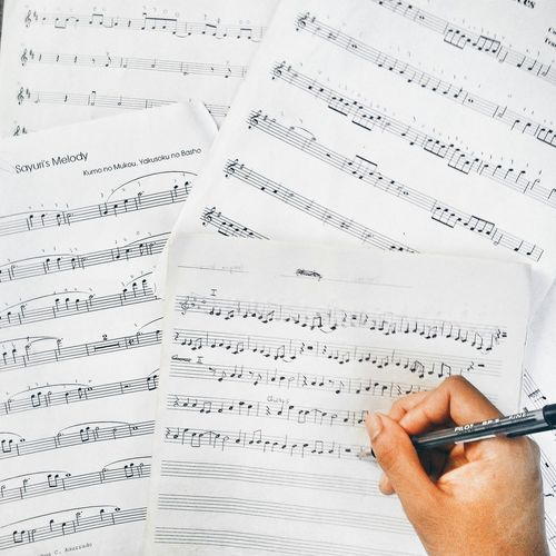 High Angle View Of Cropped Hand Writing Musical Notes