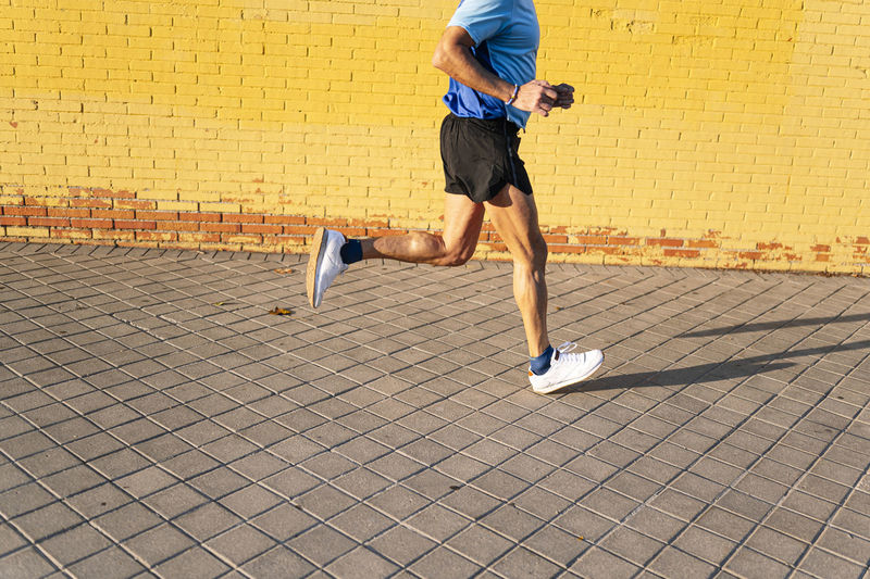 Low section of man running on cobblestone