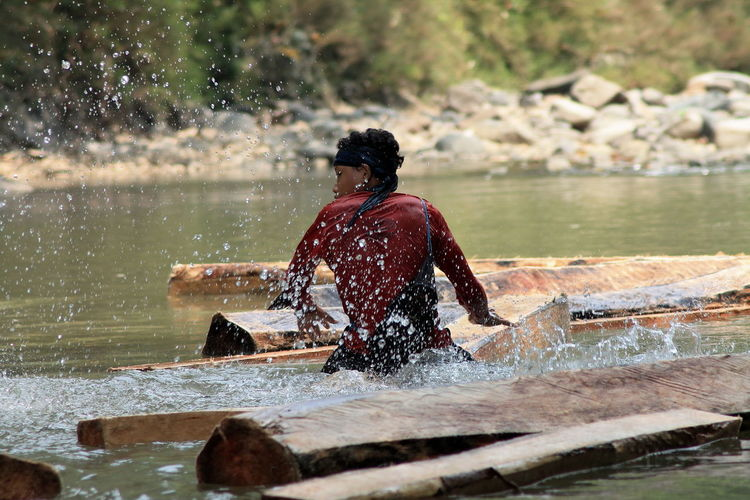 Rear view of man sitting on wood floating in river