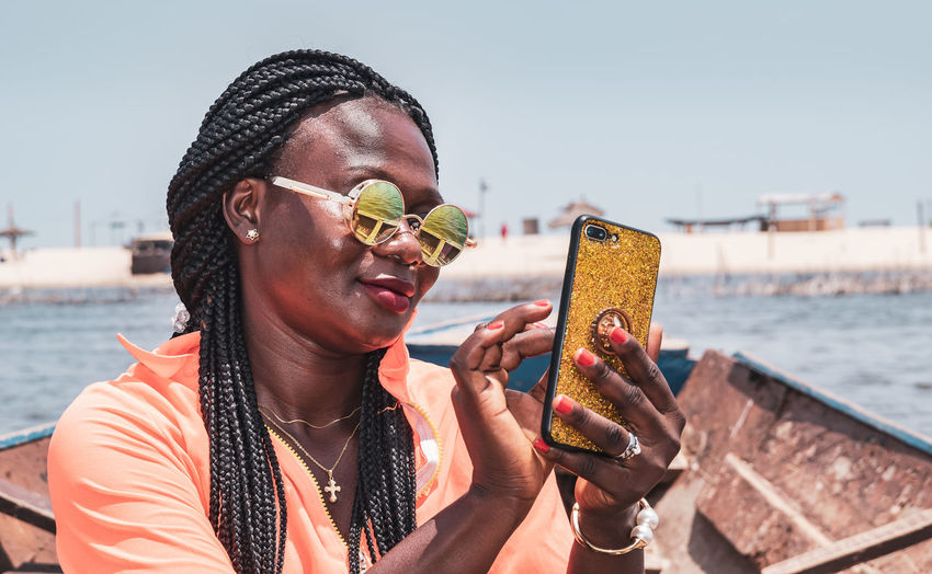 African woman sitting on a boat with mobile phone in hand and taking photos