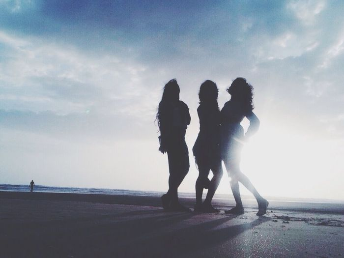 Silhouette of young women standing on beach