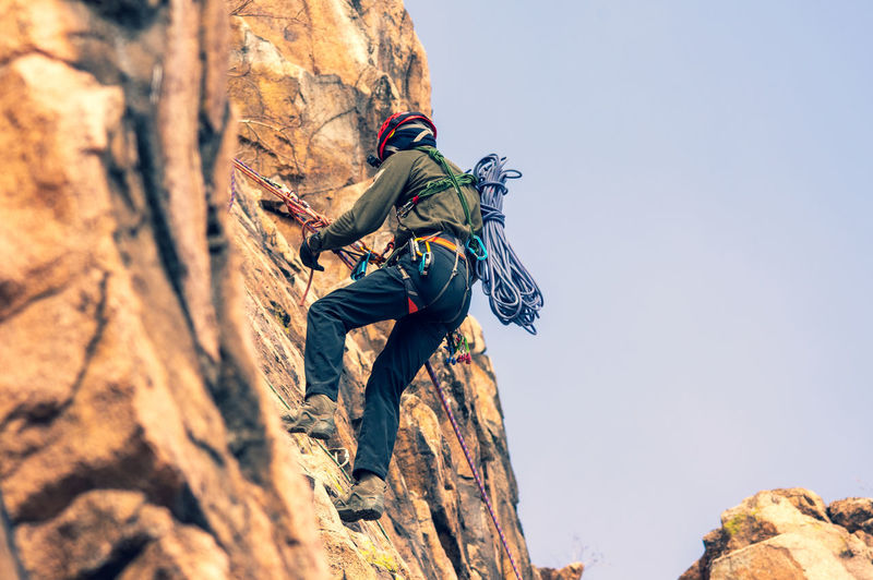 A mountaineer rappelling down the rock