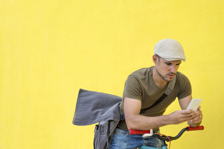 Side view of a young adult man with a vintage bike and wearing casual clothes and sunglasses standing against a yellow wall while using a mobile phone in a sunny day Yellow Wireless Technology Holding Technology One Person Communication Mobile Phone Connection Casual Clothing Young Men Telephone Young Adult Smart Phone Men Copy Space Portable Information Device Text Messaging Using Phone Lifestyles Yellow Background Outdoors Receiving Young Man Hipster Trendy Fashionable Hat T-shirt