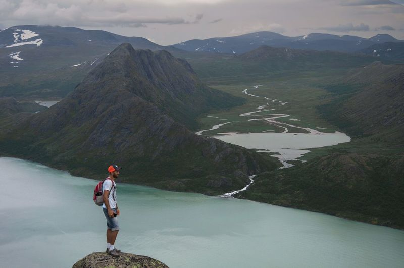 Full length of man standing on rock by lake and mountains at jotunheimen