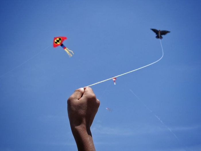 Cropped hand flying kite