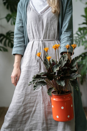 Beautiful woman standing by potted plant