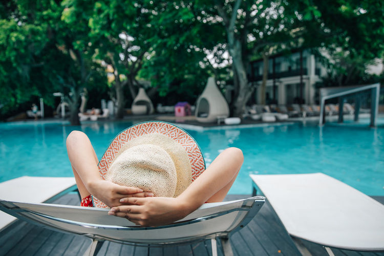 Woman relaxing on chair at swimming pool