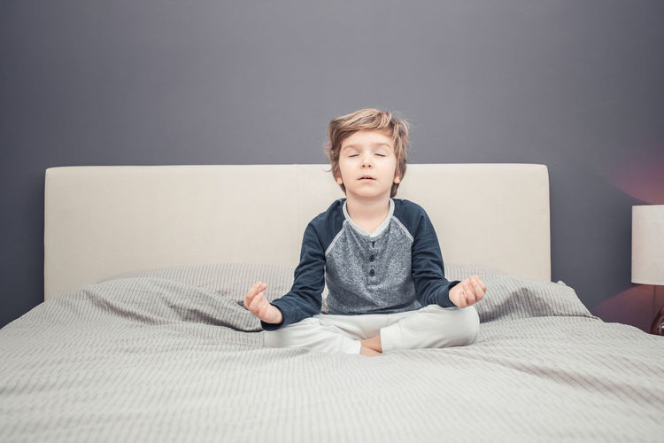 Portrait of boy sitting on bed at home