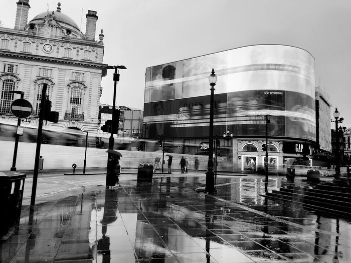 Reflection of buildings on wet street in city against sky