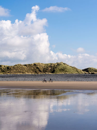 Distant view of people cycling at beach against sky