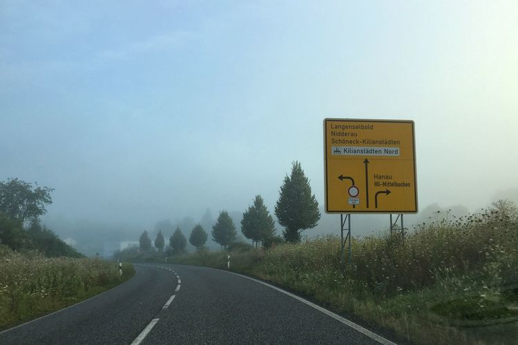 Information sign by empty road against sky during foggy weather