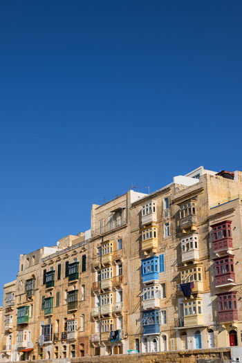 Low angle view of buildings against clear blue sky