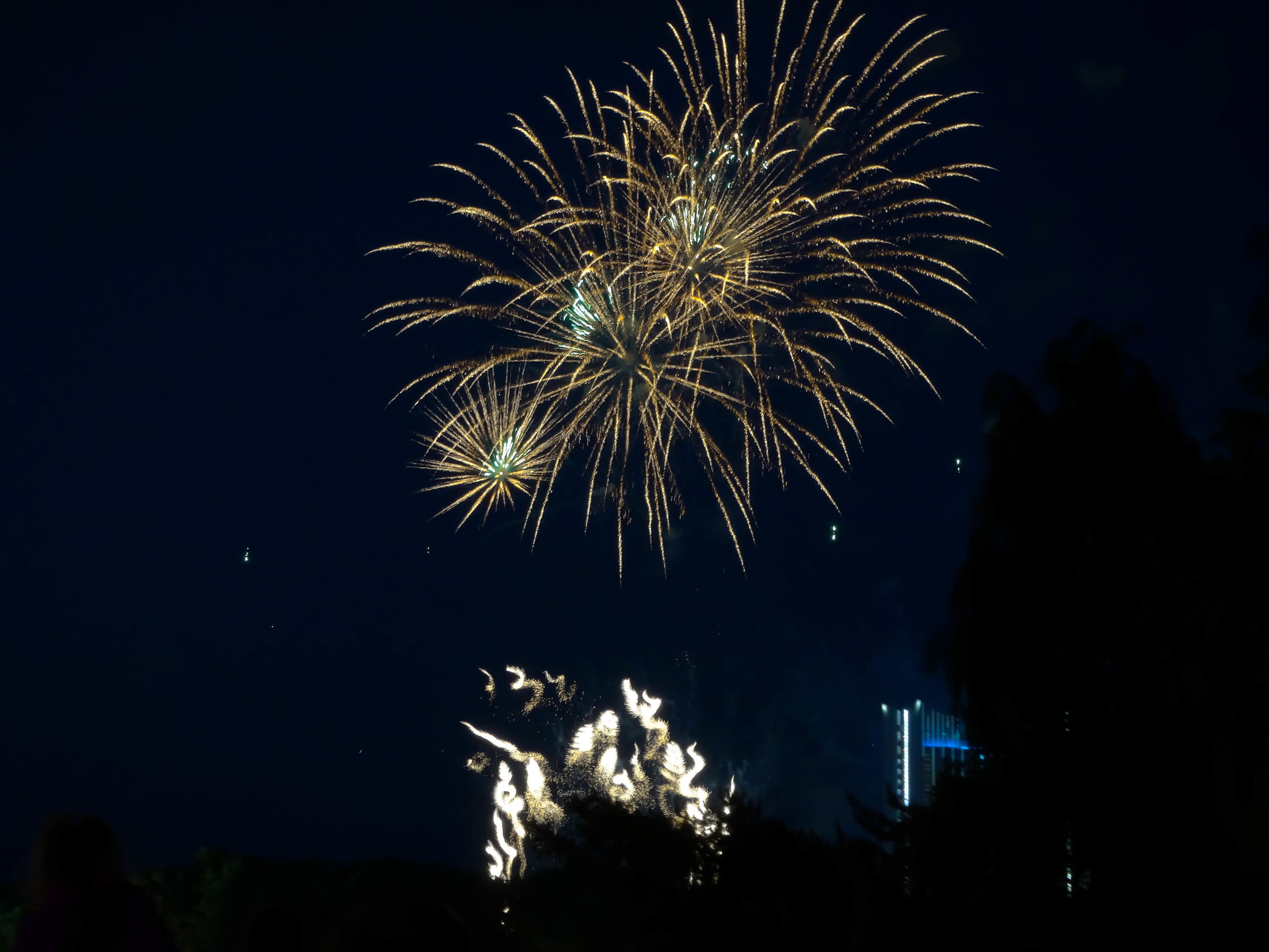 night, firework display, illuminated, exploding, celebration, firework - man made object, long exposure, arts culture and entertainment, motion, event, low angle view, sparks, glowing, firework, blurred motion, entertainment, sky, celebration event, outdoors, building exterior