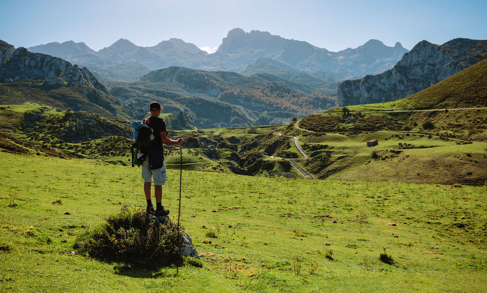 Mountaineer looking beautiful landscape with path between mountains on a sunny day Horizontal Lake Paradise Vegetation Green Landscape Scenery Mountain Scenics Lakeside Ecology Natural Grassland Field Valley Covadonga Asturias SPAIN Picos De Europa Enol Lake Ercina Lake Man One Person Unrecognizable Person Mountaineer