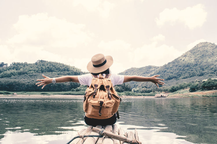 Rear view of woman with arms outstretched sitting by lake on wooden raft