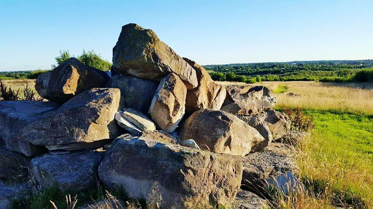 rock - object, nature, outdoors, no people, day, grass, tranquil scene, landscape, scenics, tranquility, beauty in nature, sky, clear sky, ancient civilization